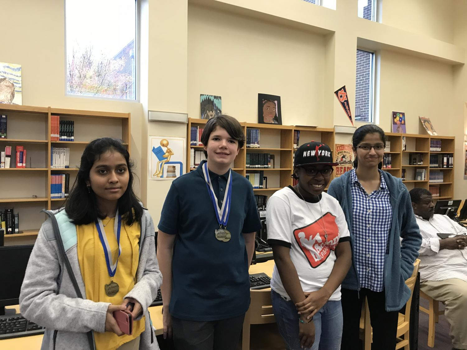 Chamblee debaters pose with a tournament judge after their December 1 competition. From left to right: freshman Tanzalia Jamal, freshman Keegan Brooks, judge Diane Sharp, and freshman Nikita Kunte.