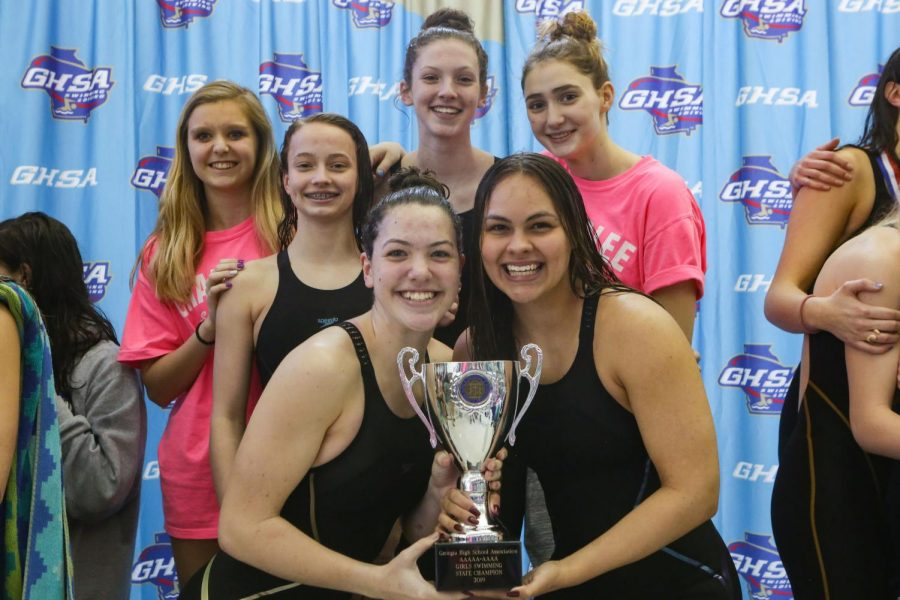 The girls' swim team poses with their trophy. From left to right, top row: Hannah Heetderks, Anna Blankenship, Kyla Maloney, Sophie Bell; From left to right, bottom row: Teresa Maloney, Jade Foelske.