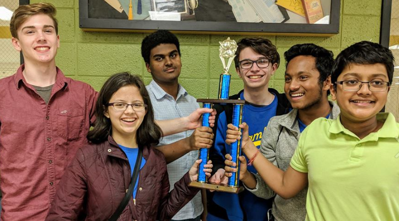 The JV Quiz Team stands showing off their 1st place trophy after the competition.