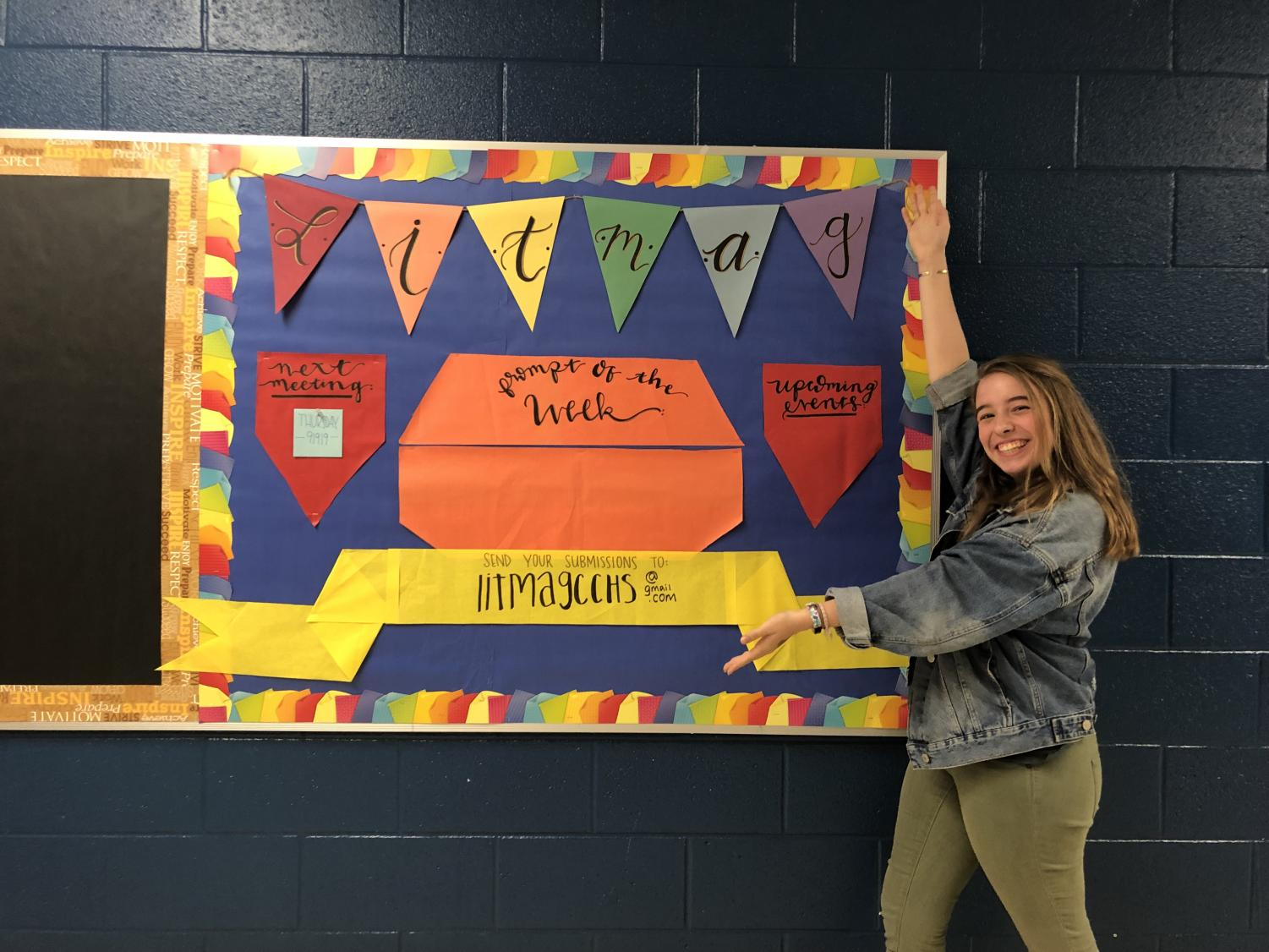 Lit mag member Lucy Roberts poses with the writing prompt board.