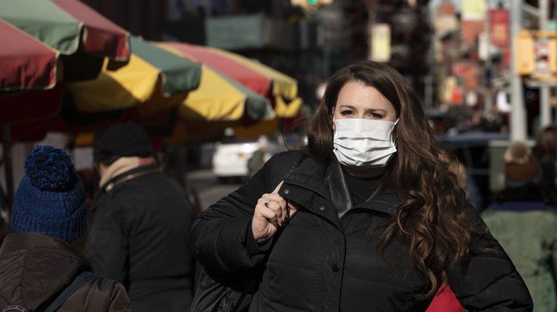 A+woman+in+New+York+wears+a+surgical+mask+amid+fears+of+coronavirus.