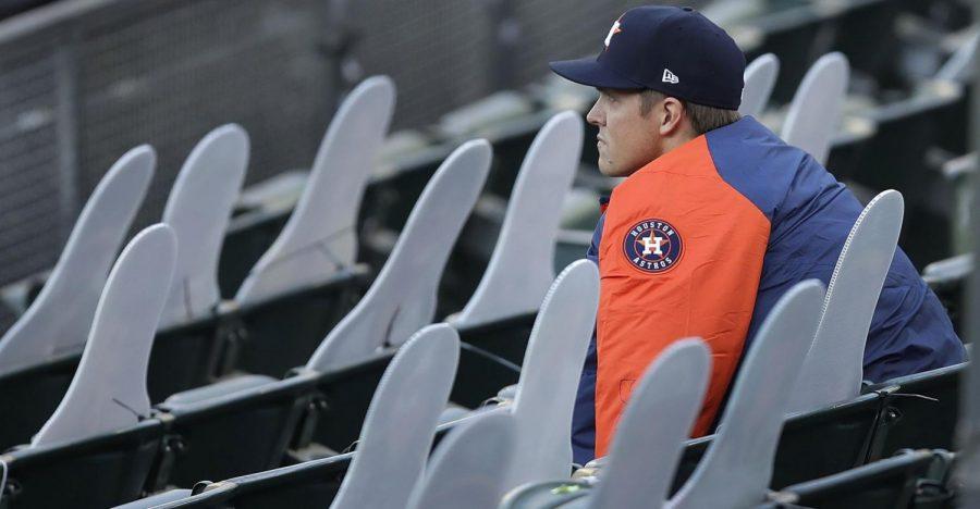Houston Astros ace Zack Greinke sitting among cardboard fan cutouts.