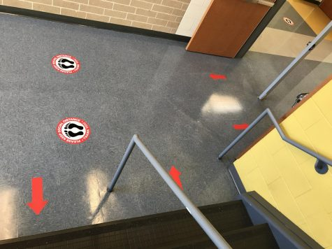 Decals on the floor indicate directions of travel in a CCHS stairwell.